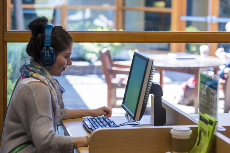 a woman using a computer and headset