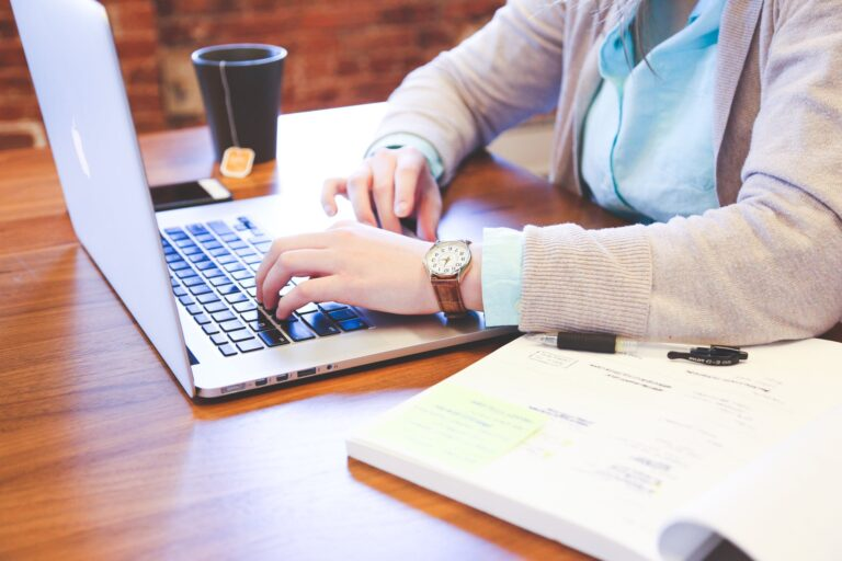 A close up shot of someone's hands typing on a laptop with a notebook and cup of tea
