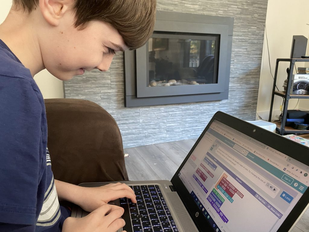 Boy doing block coding on a laptop