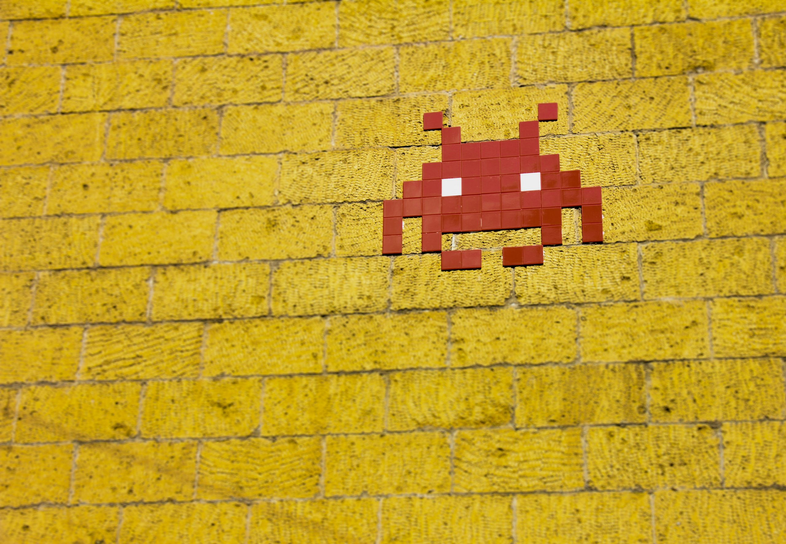 a red space invader on a yellow wall