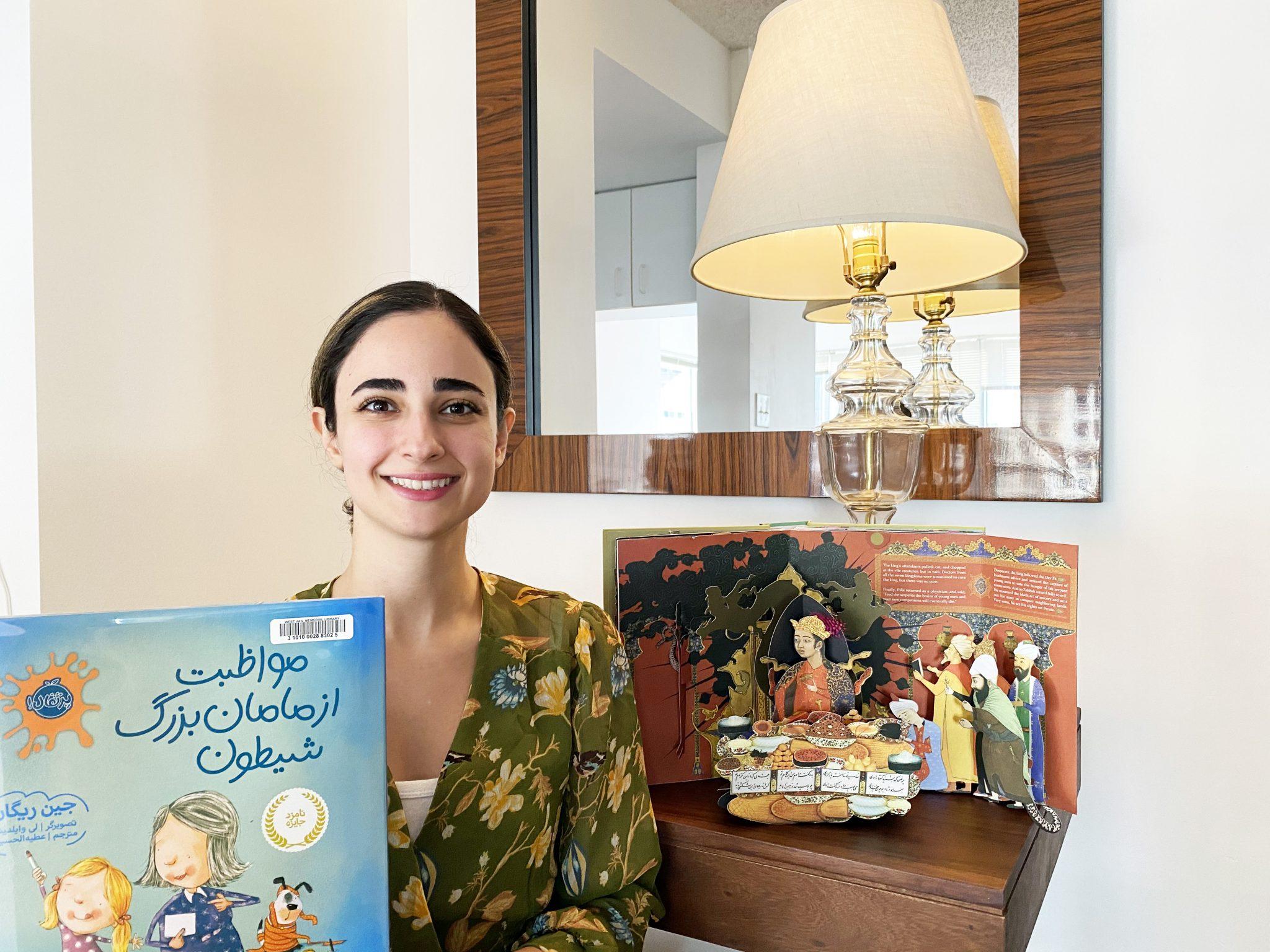 Sanam poses with two picture books in Farsi