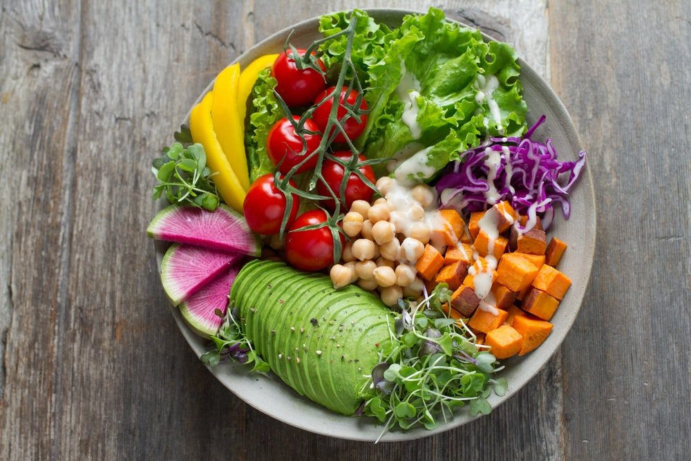 a colourful bowl of salad centred atop a wooden surface