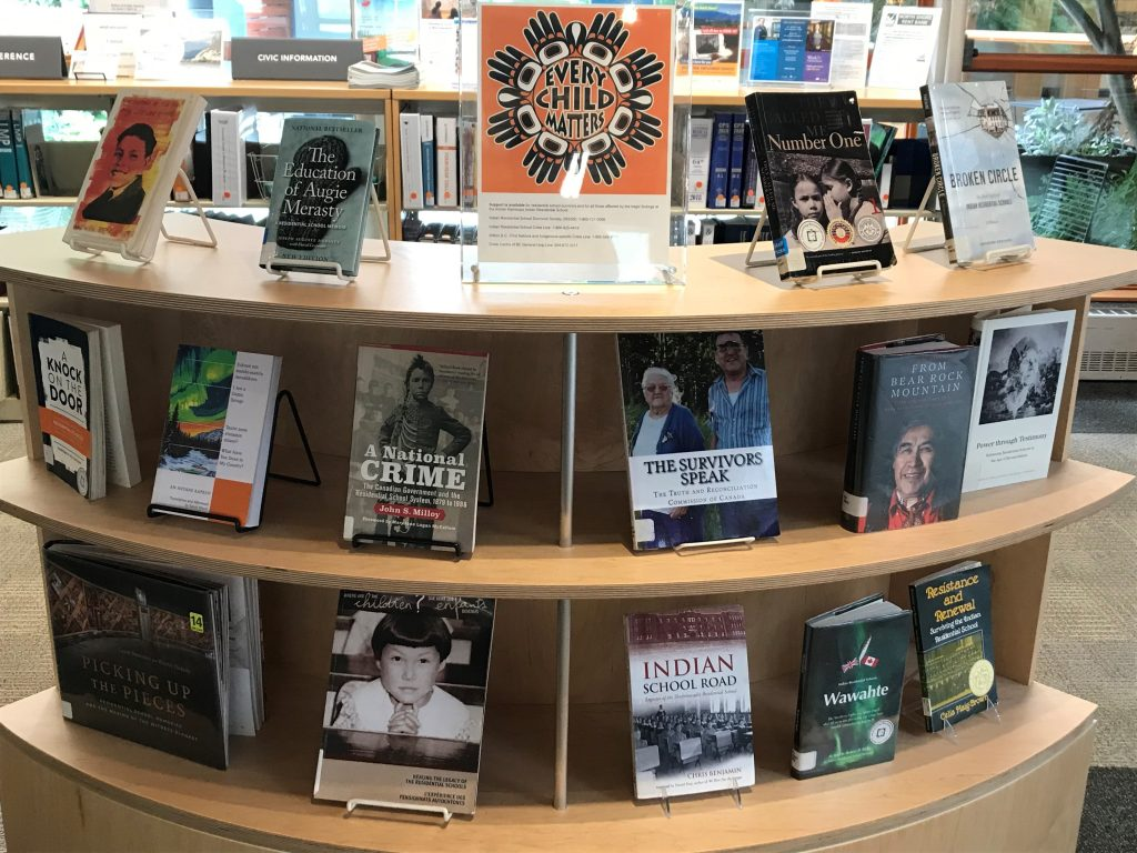 """a Library display of books about residential schools. centred at the top shelf is a sign that reads """"every child matters."""""""