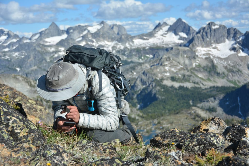 A person on a mountain bends over to photograph a plant. They are wearing a wide brimmed hat and a backpack. A mountain range is in the background.