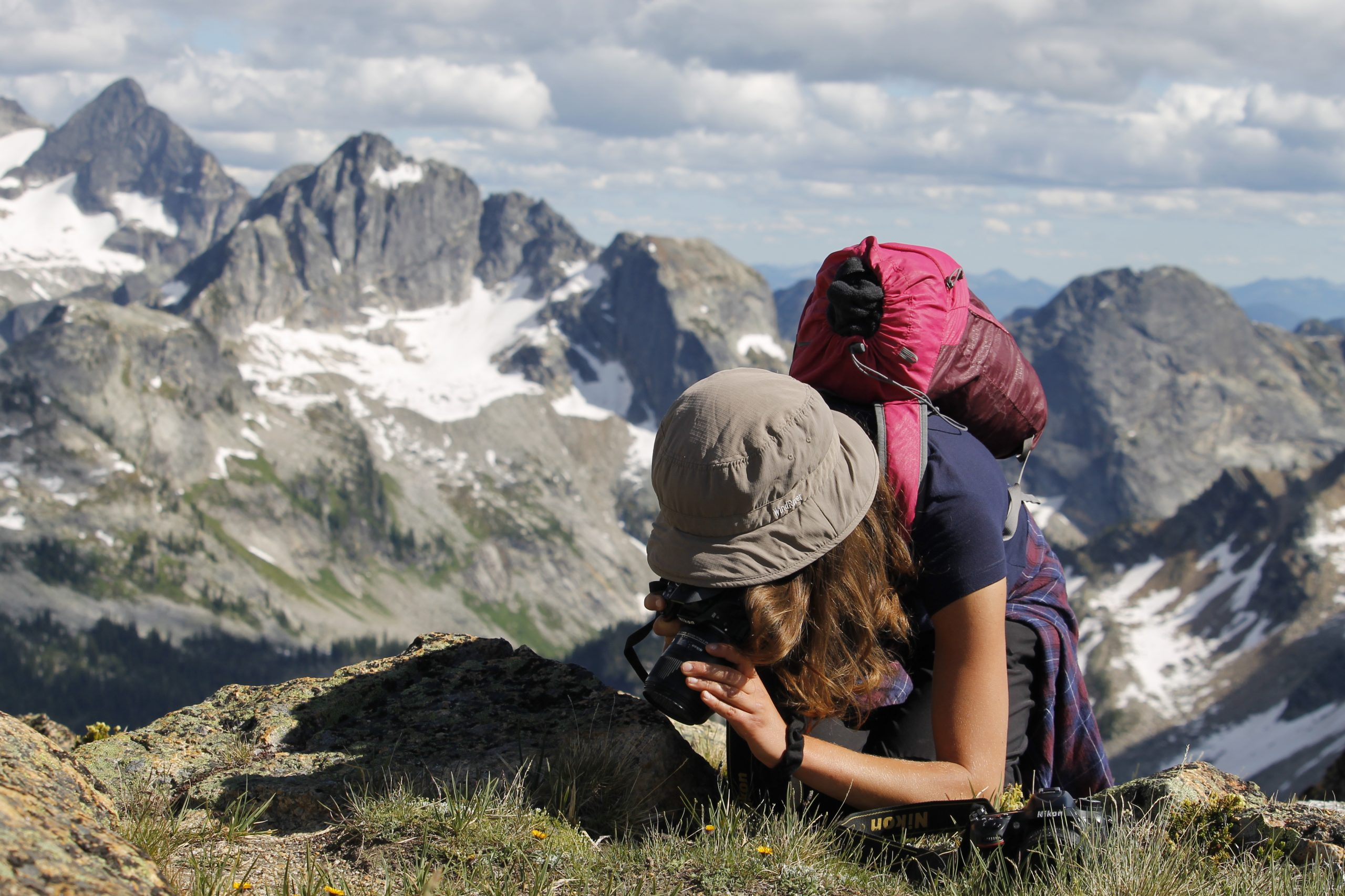 A woman on a mountain bends over to photograph a plant. She is wearing a brimmed hat and a pink backpack. A mountain range is in the background.