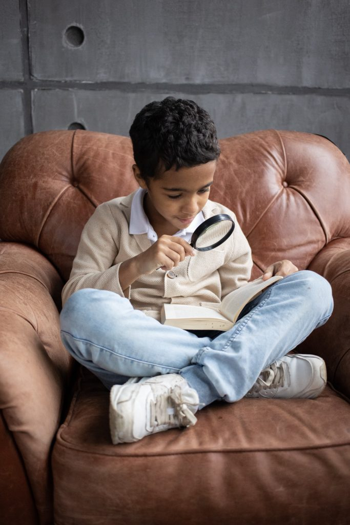 boy looking at a book with a magnifying glass