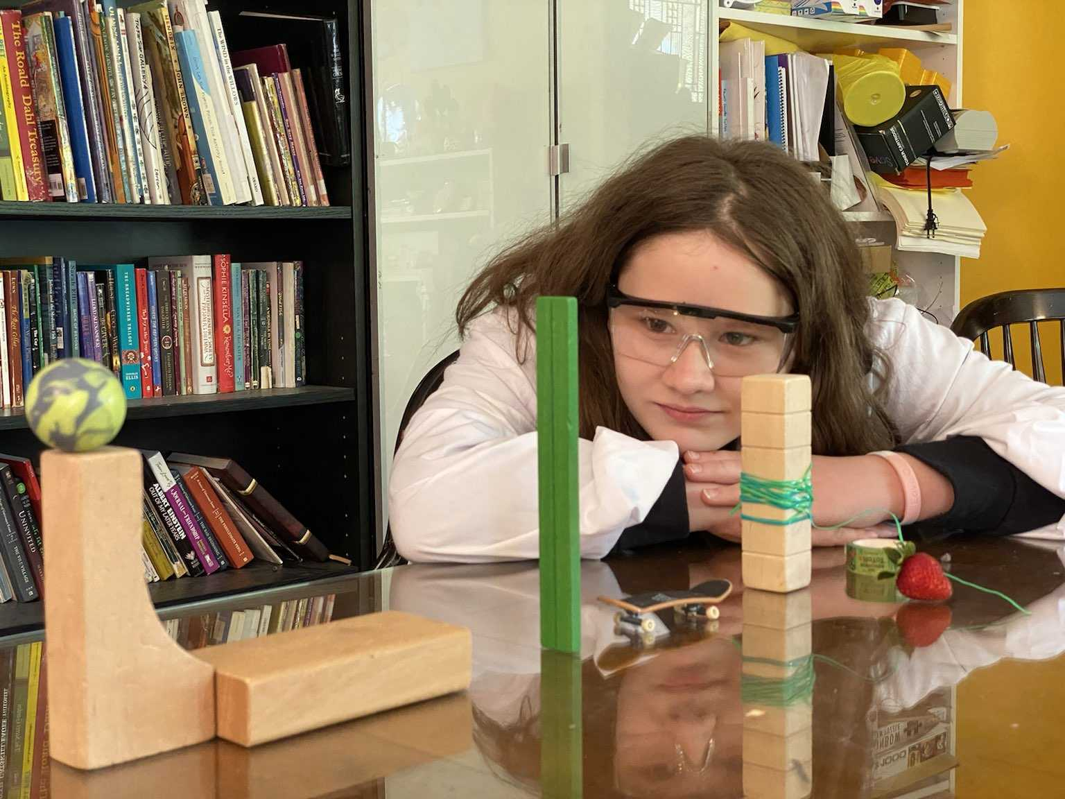 A child in a lab coat and protective eye ware ponders a Rube Goldberg machine made of blocks and toys.