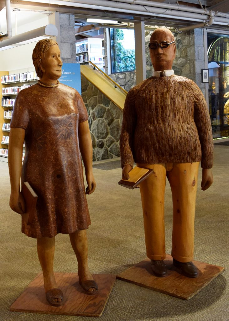 two wooden male and female sculptures, both holding books