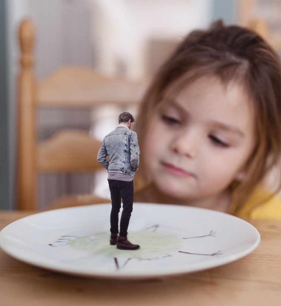 little girl looking at a small man on a plate