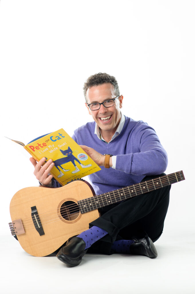 Author Eric Litwin holds a book and guitar.